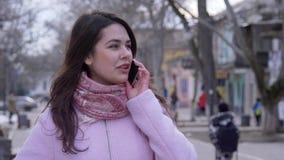 La conversazione mobile, femmina felice comunica dal telefono cellulare sul primo piano dell'aria aperta