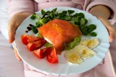 La coordonnée de la femme dans le peignoir sur le lit avec des mains tenant un plat avec le repas sain d'ajustement, nourriture i image stock