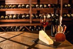 La copa de vino, el queso y los accesorios en una tabla de madera en un vino saltan Fotos de archivo