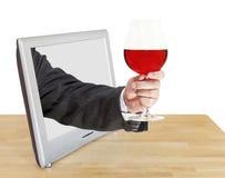 La copa de vino roja en la mano masculina inclina hacia fuera la pantalla de la TV Imagen de archivo libre de regalías