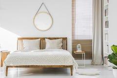 La coperta lanuginosa disposta accanto a letto matrimoniale con gli strati bianchi e tricotta Immagini Stock Libere da Diritti