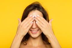 La copertura allegra sorridente della ragazza di ricerca del pellame osserva le mani immagine stock libera da diritti