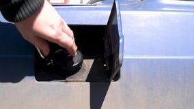 La copertura del carro armato di gas si apre su una retro automobile coperta in sporcizia dopo la corsa video d archivio