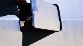 La copertura del carro armato di gas si apre su una retro automobile coperta in sporcizia dopo la corsa stock footage