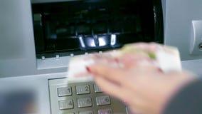 La copertura della scanalatura di BANCOMAT del primo piano apre la donna mette la banconota indietro archivi video