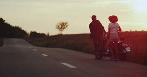 La coppia è uniformemente tutto il inlove che si tiene per mano correre nel tramonto verso la loro motocicletta, mentre la ragazz video d archivio