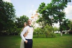 La coppia in abbigliamento di nozze è nelle mani contro il contesto del campo al tramonto, alla sposa ed allo sposo fotografia stock