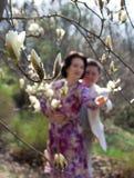 La coppia adulta cammina nel giardino sbocciante della magnolia Amore allineare Immagini Stock Libere da Diritti