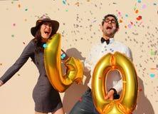 La coppia allegra celebra un compleanno di quaranta anni con i grandi palloni dorati e piccoli pezzi di carta variopinti nell'ari Immagine Stock Libera da Diritti