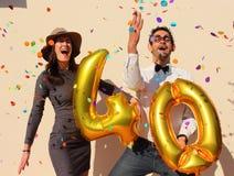 La coppia allegra celebra un compleanno di quaranta anni con i grandi palloni dorati e piccoli pezzi di carta variopinti nell'ari Fotografie Stock Libere da Diritti