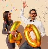 La coppia allegra celebra un compleanno di quaranta anni con i grandi palloni dorati e piccoli pezzi di carta variopinti nell'ari Immagini Stock Libere da Diritti