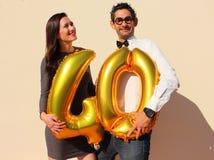 La coppia allegra celebra un compleanno di quaranta anni con i grandi palloni dorati e piccoli pezzi di carta variopinti nell'ari Fotografie Stock