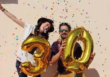 La coppia allegra celebra un compleanno di trenta anni con i grandi palloni dorati Immagine Stock