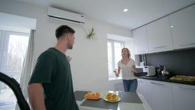 La coppia allegra in cucina che imbroglia intorno, tipo gioca l'aspirapolvere come una chitarra vicino ad una ragazza che balla c