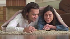 La coppia allegra nell'amore che si trova sul tappeto nella camera da letto coperta di coperta che legge un libro e allegramente  stock footage