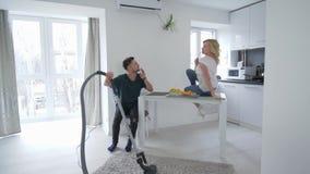 La coppia allegra sta imbrogliando intorno in cucina, tipo sta ballando con un aspirapolvere con una ragazza che canta con un cuc