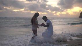 La coppia amorosa felice vicino all'oceano, ragazzo ottiene su un ginocchio e presenta una proposta video d archivio