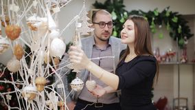La coppia amorosa seleziona le decorazioni di Natale nel supermercato Una donna che considera il Natale palle ed offerte archivi video