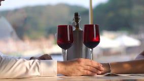 La coppia amorosa sta avendo data romantica Stanno tenendo per mano tenero ai precedenti dei bicchieri di vino Nessun fronte stock footage