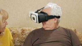 La coppia anziana prova la realtà virtuale di vetro a casa L'uomo indossa i vetri e ridono di che cosa sta accadendo alto stock footage