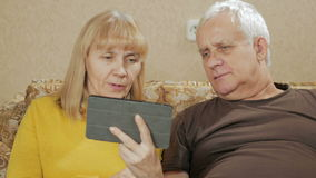 La coppia anziana suona sui video collegamenti sulla compressa Marito e moglie che si siedono a casa sullo strato Il concetto di stock footage