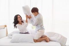 La coppia asiatica si siede sul letto, essi ha lotta di cuscino fotografia stock