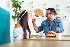 La coppia bella nell'amore sta sedendosi in caffè Il giovane sta alimentando la suoi donna e sorridere fotografia stock