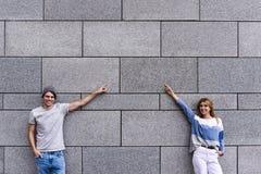 La coppia bella sta indicando via e sorridere, stante contro la parete grigia immagine stock libera da diritti
