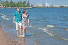 La coppia cammina sulla spiaggia Immagine Stock