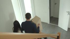 La coppia caucasica scala le scale e porta le scatole di cartone in loro mani che si muovono verso un nuovo appartamento video d archivio