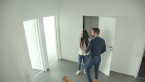 La coppia caucasica scala le scale ed esamina intorno un nuovo appartamento