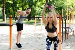La coppia caucasica sportiva sta scaldandosi prima della formazione in un parco Fotografia Stock