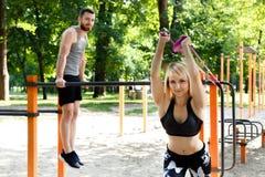 La coppia caucasica sportiva sta scaldandosi prima della formazione in un parco Immagine Stock Libera da Diritti