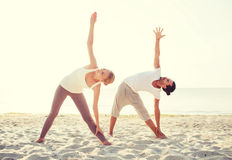 La coppia che fa l'yoga si esercita all'aperto Fotografia Stock