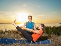 La coppia che fa l'yoga si esercita all'aperto Immagine Stock Libera da Diritti