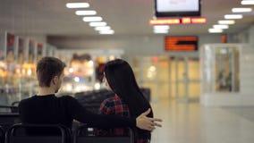 La coppia della gente attivamente parla a vicenda la seduta nell'aeroporto stock footage