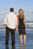 la coppia della spiaggia passa la donna dell'uomo della holding Fotografie Stock Libere da Diritti