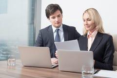 La coppia di affari sta controllando due volte alcune informazioni essenziali di affari immagine stock
