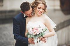 La coppia di nozze è stante e baciante nelle vie di vecchia città Fotografie Stock