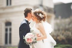 La coppia di nozze è stante e baciante nelle vie di vecchia città Immagini Stock Libere da Diritti