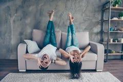 La coppia divertente con gesturing di vetro sta trovandosi sottosopra sul immagine stock