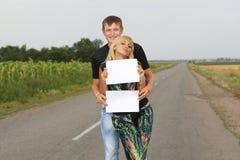 La coppia divertente mostra pezzo di carta in bianco Immagini Stock Libere da Diritti