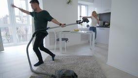 La coppia divertente nell'amore sta imbrogliando intorno in cucina, il tipo sta ballando con un aspirapolvere e una ragazza biond