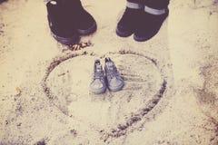 La coppia fa l'annuncio del bambino con un paio delle scarpe minuscolo fuori Fotografia Stock