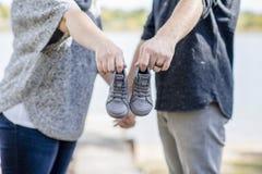 La coppia fa l'annuncio del bambino con un paio delle scarpe minuscolo fuori Fotografie Stock Libere da Diritti