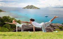 La coppia felice che fa l'yoga si esercita all'aperto Fotografia Stock