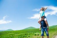 La coppia felice, ragazza che si siede sull'uomo mette Fotografie Stock