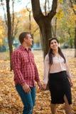 La coppia felice sta camminando nel parco della città di autunno Alberi gialli luminosi fotografie stock libere da diritti