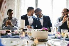 La coppia gay passa la torta nunziale di taglio Fotografia Stock Libera da Diritti