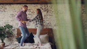 La coppia giovane divertente sta ballando sul letto divertendosi nell'hotel e nella risata Gente felice, vacanza, stile di vita m archivi video